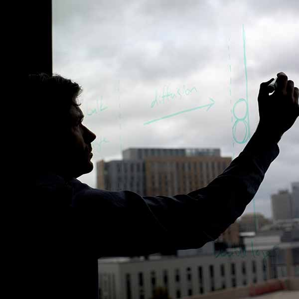 shadow of man writing processes formula on window overlooking city skyline