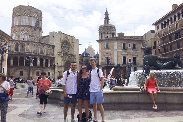 three students posing in city square in Spain