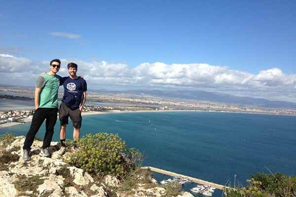 two students on cliff overlooking body of water