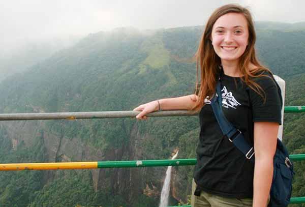 student on bridge overlooking mountains in India