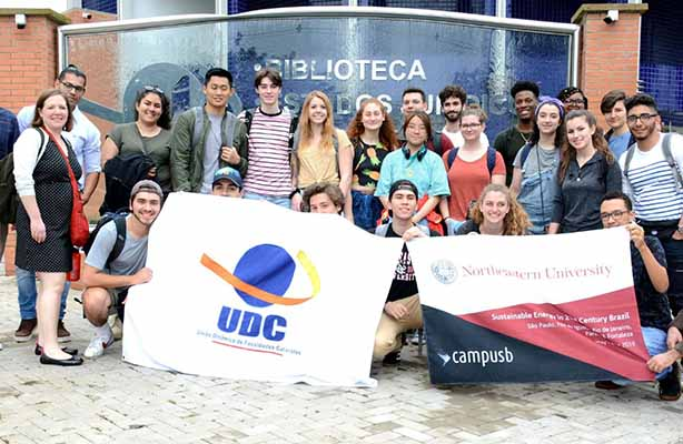 group of students pose with Brazil banner on a group trip in that country.